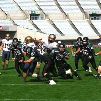 Gang star: A Kyoto University defender tries to bring down the ball carrier during a 2013 game against the Kansai University Kaisers at Nagai Stadium in Osaka. | KAZ NAGATSUKA