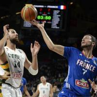 Consolation prize: France's Joffrey Lauvergne (right) vies for the ball with Lithuania's Jonas Valanciunas during France's 95-93 win on Saturday. | AFP-JIJI
