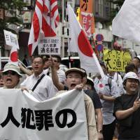 Worrisome words: In this photo taken May 19, 2013, nationalist protesters with flags march through Tokyo to denounce 'privileges' for Korean residents in Japan. Some of the demonstrators were heard shouting, 'Kill Koreans.' | AP
