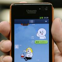 Line up for cash: A person uses the Line messaging app with a friend. Line is a South Korean success story and its impending IPO is expected to bring in more than ¥1 trillion. | KYODO