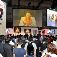 Crime doesn't pay: Sega producer Toshihiro Nagoshi (center) gives a presentation on his forthcoming game, 'Yakuza 0.' Despite the 'Yakuza' series' huge success in Japan, sluggish sales in the West have led to recent instalments not coming out  in English. | YOSHIAKI MIURA