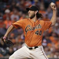 Larger than life: Giants starter Madison Bumgarner pitches against the Dodgers on Friday in San Francisco. The left-hander picked up his 18th win in the Giants' 9-0 blowout. | AP