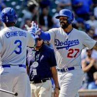 Flying start: Los Angeles' Matt Kemp (right) celebrates with teammate Carl Crawford after hitting a three-run home run in the first inning of the Dodgers' 14-5 win over the Cubs on Friday. | REUTERS/USA TODAY SPORTS