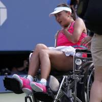 Helping hand: Peng Shuai is taken off the court during her U.S. Open semifinal on Friday. | REUTERS
