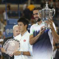 Marin Cilic poses Monday with the championship trophy alongside Kei Nishikori after the final match of the 2014 U.S. Open tennis tournament.   AP