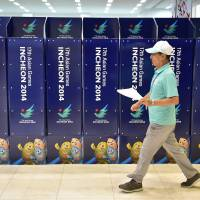Ready to go: A volunteer walks past logos for the Asian Games in Incheon, South Korea, on Wednesday. | AFP-JIJI