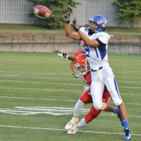 Appliance of science: Nippon Sports Science University wide receiver Genta Nakano receives a pass from Yota Tsuji as Nihon University defensive back Ken Inoue covers him during the first quarter on Saturday at Amino Vital Field. Nihon Sports Science University won 56-14. | HIROSHI IKEZAWA