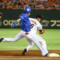 First line of defense: Yomiuri pitcher Tetsuya Utsumi (right) gets Yokohama's Takehiro Ishikawa out at first base during the Giants' 4-0 win over the BayStars on Friday.   KYODO