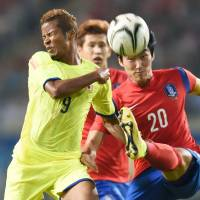 High octane: Striker Musashi Suzuki (left) braces for impact during Japan's 1-0 quarterfinal defeat to South Korea at the Asian Games on Sunday. | KYODO