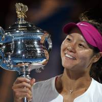 Defining moment: China's Li Na holds the championship trophy after defeating Dominika Cibulkova of Slovakia in their women's singles final at the 2014 Australian Open in January. Li announced her retirement on Friday. | AP