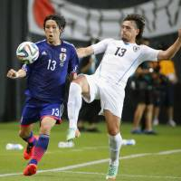 Keeping it close: Uruguay's Matias Aguirregaray (right) and Japan's Hajime Hosogai vie for the ball during Friday's international friendly in Sapporo. Uruguay defeated Japan 2-0.  | KYODO