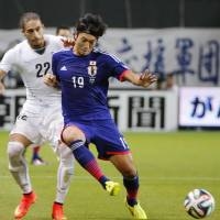 Ball control: Japan's Yusuke Minagawa (19) and Uruguay's Martin Caceres battle for position during Friday's match.  | KYODO