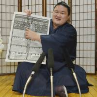 Climbing the ladder: Newly promoted ozeki Goeido points to his name in the rankings for the Autumn Grand Sumo Tournament on Monday. | KYODO