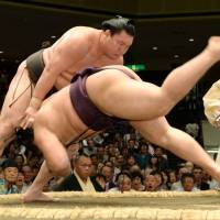 Hit the deck: Hakuho shoves Endo down during the second day of the Autumn Grand Sumo Tournament on Monday. | KYODO
