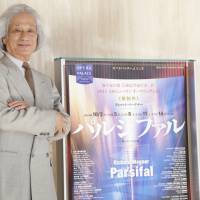 Set the stage: Maestro Taijiro Iimori stands next to a poster for the 'Parsifal' production he will conduct at the New National Theatre, Tokyo. Iimori is widely considered an expert in conducting the works of Richard Wagner. | CHIEKO KATO