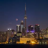 The moon turns orange during a total lunar eclipse behind the CN Tower and the skyline during moonset in Toronto Wednesday. The eclipse is also known as a 'blood moon' due to the coppery, reddish color the moon takes as it passes into Earth's shadow.  | REUTERS