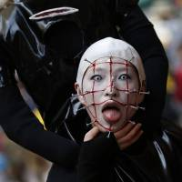 A participant in costume poses for a picture before a Halloween parade Sunday in Kawasaki. More than 100,000 spectators turned up to watch the parade of 2,500 participants, according to the organizer. | REUTERS