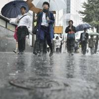 Puddles form along the streets of Shinjuku Monday morning as Typhoon Phanfone heads for Tokyo. | KYODO