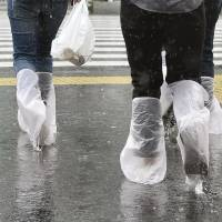 Commuters in Shinjuku improvise with plastic bag galoshes as Typhoon Phanfone dropped heavy rains on the city Monday morning.   | KYODO