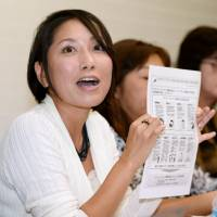 Victorious: A member of Mata-Hara Net, a support group for victims of 'maternity harassment,' speaks at a news conference in Tokyo after the Supreme Court's landmark ruling on Oct. 23.   KYODO
