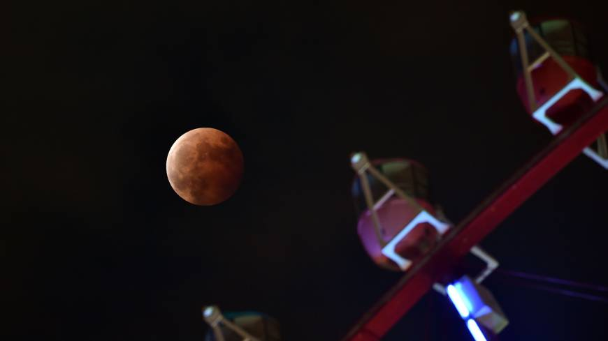 A total lunar eclipse is seen above a ferris wheel in Tokyo on Wednesday.