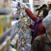 Customers browse the dairy section at a Lawson Mart Inc. convenience store in Yokohama in February. Japanese companies are forecasting annual inflation of 1.5 percent in a year, the Bank of Japan said on Thursday in Tokyo.   BLOOMBERG