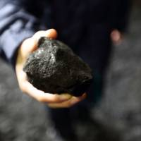 An employee holds a piece of coal in a storage yard at the Joban Joint Power Co. Nakoso coal-fired power station in Iwaki, Fukushima Prefecture, on Feb 6. | BLOOMBERG