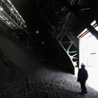 An employee stands inside a coal storage yard at the Joban Joint Power Co. Nakoso coal-fired power station in Iwaki, Fukushima Prefecture, on Feb 6. | BLOOMBERG