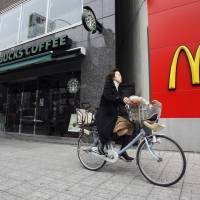 A woman rides past a Starbucks and a McDonald's in Tokyo's Jinbocho district in a March 2007 file picture. The success of those two chains in selling coffee has inspired convenience store operators to offer their own premium brews. | REUTERS