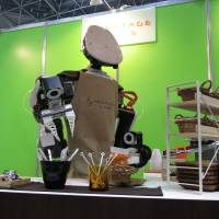 Kawada Industries Inc.'s industrial robot Nextage serves coffee to visitors during the Japan Robot Week exhibition at Tokyo Big Sight in the Odaiba district. | KAZUAKI NAGATA