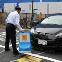A user of the Park24 Co. sharing service prepares to take out a vehicle in Minato Ward, Tokyo, last Thursday. | YOSHIAKI MIURA
