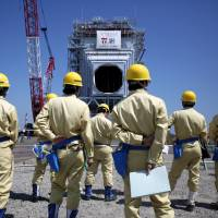 Workers look at a heat recovery steam generator boiler module made by Mitsubishi Hitachi Power Systems Ltd. as it is rolled off a barge at Tokyo Electric Power Co.'s combined cycle thermal power station in Kawasaki in August. | BLOOMBERG