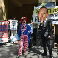 Protesters gather Saturday outside the Sydney hotel where trade ministers were trying to advance negotiations on the Trans-Pacific Partnership. | AFP-JIJI