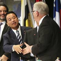 Akira Amari, minister in charge of the Trans-Pacific Partnership negotiations, shakes hands with Australia's trade minister Andrew Robb while wrapping up a news conference Monday after the latest round of marathon trade talks. | AP
