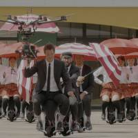 With the drone flying overhead, OK Go with school girls in tow, glide through the stadium courtyard. | COURTESY OF OK GO