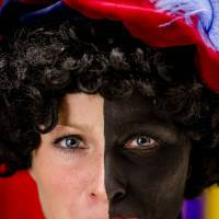 A woman has her face painted to become Black Pete on Wednesday in Soest, the Netherlands. | AFP-JIJI