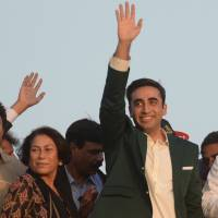 Bilawal Bhutto Zardari waves upon arriving for a public gathering in Karachi on Saturday. Beside him is Sanam Bhutto, daughter of the late Prime Minister Zulfiqar Ali Bhutto and sister of the late Prime Minister Benazir Bhutto. | AFP-JIJI