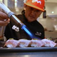 Taro Arai, executive chef of Mikuni Restaurant Group, uses a torch to sear a piece of sushi in Sacramento, California, on Oct. 10. | AP