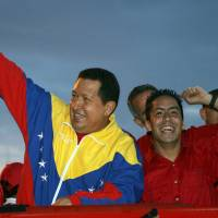 Then-Venezuelan President Hugo Chavez (left) and the candidate of their party for the parliamentary elections Robert Serra greet supporters during a rally in Caracas in 2010. Serra was found slain at his home in Caracas on Thursday. | AFP-JIJI