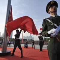 A paramilitary policeman unfurls a Chinese national flag during a ceremony to mark the 65th anniversary of the founding of the People's Republic of China, in Hefei, Anhui province, on Wednesday. This year, the annual holiday was overshadowed in Hong Kong by sprawling pro-democracy protests, in the largest popular challenge to the ruling Communist Party in years. | REUTERS