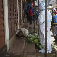 Health workers collect samples from the corpse of a suspected Ebola victim in Freetown on Oct. 8.   AP