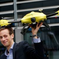 Graduated TU Delft student Alec Momont shows his design of an ambulance drone with a built in defibrillator in Delft, Holland,  on Tuesday. The small aircraft, designed by Momont of the Delft Technical University, weighs some 4 kg and can fly at the speed of 100 kph and can quickly deliver a defibrillator to patients suffering from a heart attack. | AFP-JIJI
