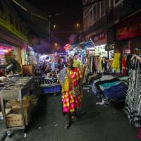 A woman walks through a market in the 'African village' in Guangzhou, the capital of the Chinese province of Guangdong, on Oct. 25. | REUTERS
