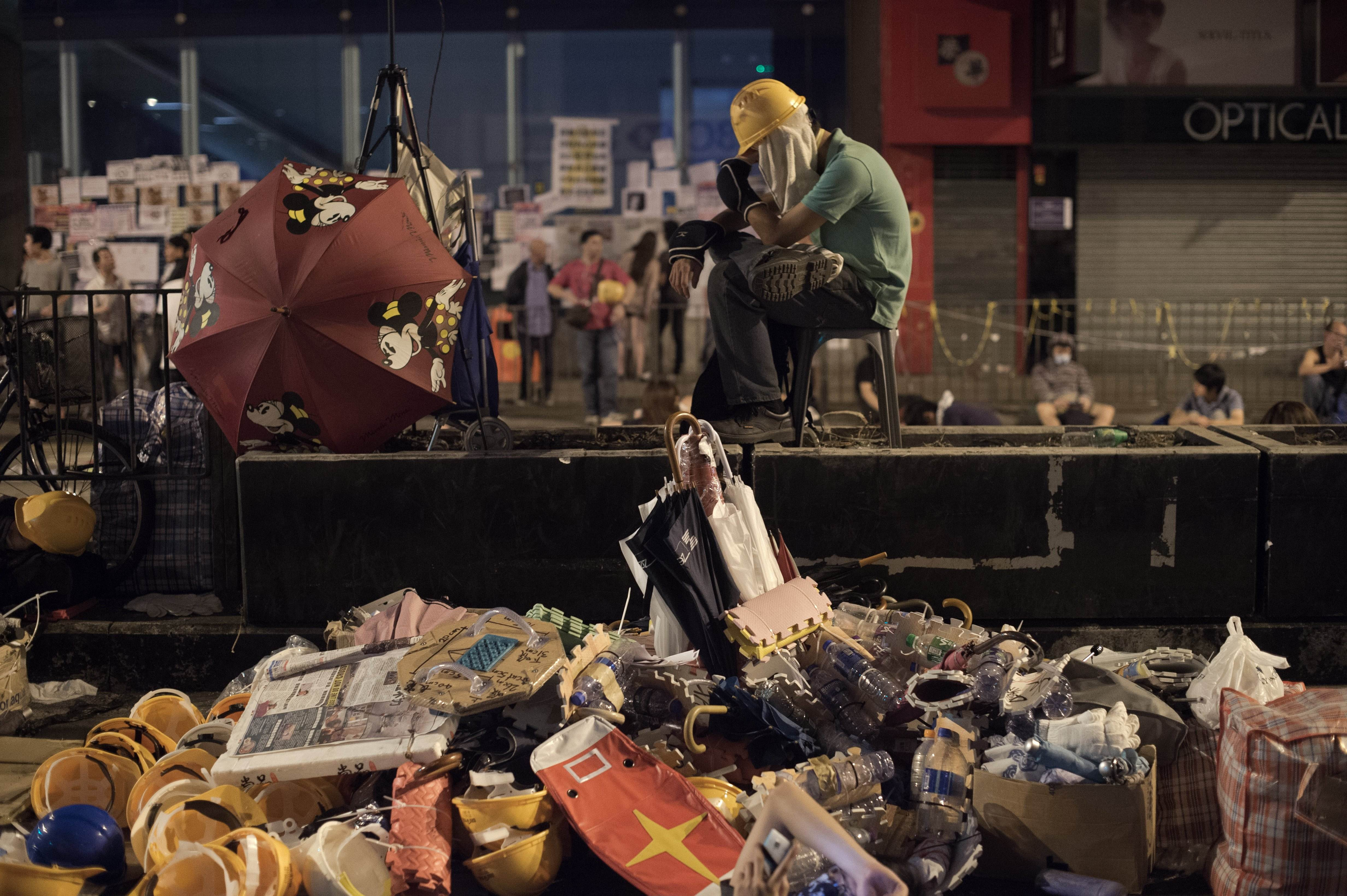 A pro-democracy protester sits inside barricades in the Mong Kok district of Hong Kong early Tuesday. Pro-democracy leaders Monday angrily denied claims by the city's chief executive that 'external forces' are orchestrating their mass rallies, ahead of talks intended to end three weeks of political stalemate. | AFP-JIJI
