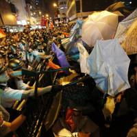 Riot police clash with pro-democracy protesters at the Mongkok district of Hong Kong in the early hours of Sunday. Hong Kong pro-democracy activists recaptured parts of the core protest zone early Saturday, defying riot police who had tried to disperse them with pepper spray and baton charges. | REUTERS