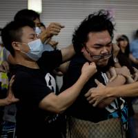 Men try to force Hong Kong protesters off streets