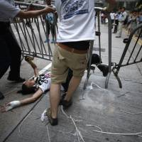 Anti-Occupy Central protesters drag a metal fence over a pro-democracy protester Monday at the main protest site in Admiralty in Hong Kong. Hundreds of unidentified people, some wearing masks, tried to break down protest barriers in the heart of Hong Kong's business district on Monday, scuffling with protesters who have occupied the streets for the past two weeks. | REUTERS
