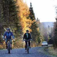 Nurse Kaci Hickox and her boyfriend, Ted Wilbur, are followed by a Maine State Trooper as they ride bikes on a trail near their home in Fort Kent, Maine, Thursday.  State officials are going to court to keep Hickox in quarantine for the remainder of the 21-day incubation period for Ebola that ends on Nov. 10. Police are monitoring her, but can't detain her without a court order signed by a judge. | AP