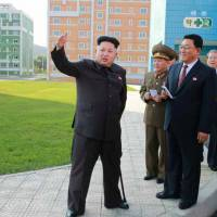 North Korean leader Kim Jong Un (left) leans on a cane during an inspection tour of a newly built housing complex in Pyongyang in this picture taken from Tuesday's edition of the Rodong Sinmun daily. | AFP-JIJI