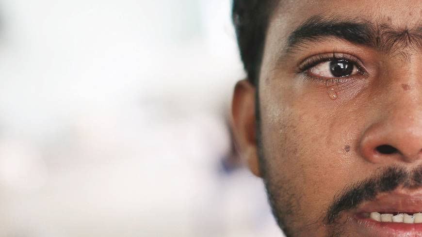 Muhammed Ariful Islam, a Bangladeshi painter who was abducted and held captive on a prison ship before being abandoned on a remote island, cries on Oct. 17 at a government shelter in Thailand's Phang Nga province, north of Phuket. | REUTERS